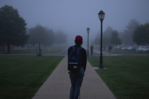 Student walking down foggy street